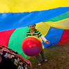 Record-Eagle/Jan-Michael Stump<br /> Hunter Conlon, 5, of Traverse City plays under a parachute with his mother Noma Stewart during Fun and Games for Special Kids at the Open Space Wednesday at the National Cherry Festival.