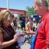 "Record-Eagle/Douglas Tesner<br /> Carla Westervelt purchases a ""Go For The Gold"" pin from volunteer salesman Peter Garthe."