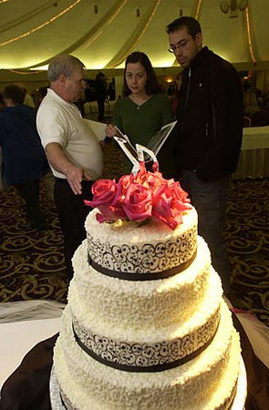 Record-Eagle/Garret Leiva<br /> Traverse City residents Janelle Mowat and Ron Koontz make plans for their March wedding as they speak with Terry Pendock about the cakes created by his wife, Lynda Pendock of Kingsley Cakes.