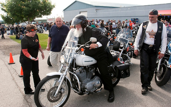 "Record-Eagle/Douglas Tesner<br /> <br /> Under the careful of eyes of members of the Northern Chapter Harley Owners Group, Rev Iakovos Olechnowicz parks his bike before the start of 18th Annual HOG ""Ride for Father Fred"" benefiting the Father Fred Foundation."