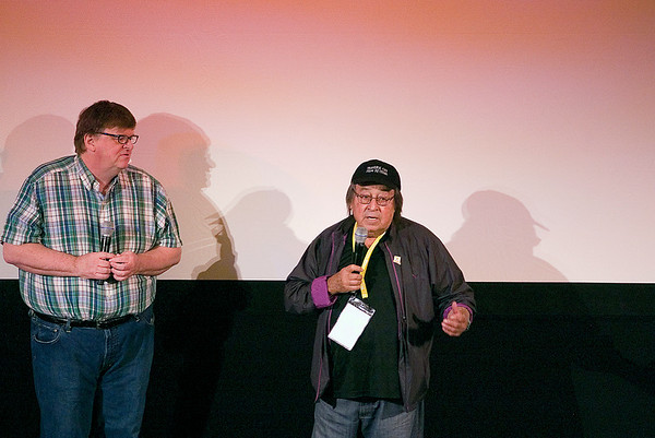 "Record-Eagle photo/Jan-Michael Stump<br /> Michael Moore, left, listens to director Paul Mazursky as he speaks to the audience at the City Opera House before the start of Wednesday evening's screening of ""Enemies, A Love Story."""
