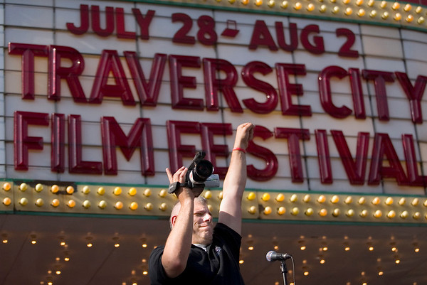 Record-Eagle photo/Jan-Michael Stump<br /> Mark Dragovich celebrates with the crowd after recording video for the Traverse City Film Festival as it kicked off its fifth year with opening ceremonies outside the State Theatre on a blocked off Front Street. Traverse City filmmaker Rich Brauer was presented the Michigan Filmmaker Award.