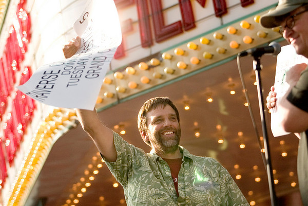 Record-Eagle photo/Jan-Michael Stump<br /> Traverse City filmmaker Rich Brauer tears the ceremonial first ticket after being presented the Michigan Filmmaker Award at the opening cermonies of the fifth annual Traverse City Film Festival outside the State Theatre on a blocked off Front Street.