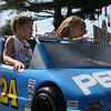 Record-Eagle/Laura Wright<br /> Savannah Anderson, 4, and her brother, Gavin, 6, of Traverse City, enjoy a ride on the race cars during Special Kids Day.