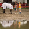 Record-Eagle photo/Jan-Michael Stump<br /> Isa Fiebing, 11, of Traverse City, left, and Amanda Rottman, 12, of Williamsburg take Fiebing's horse Besito through a coral Sunday at the Northwestern Michigan Fair.