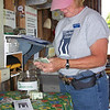 Darlene counting donations, selling items in gift shop and collecting camping fees.