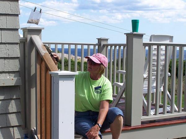 Darlene paints railing on back porch.