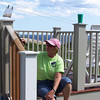 Darlene paints railing on back porch.