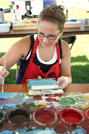 Record-Eagle/Keith King<br /> Maggie Lazarowicz, 15, of Bay City, paints a piece of tile near the Open Space Saturday, July 3, 2010 during the National Cherry Festival in Traverse City. The tile was being painted as part of the Community Mural Project that will result in a 13 foot by 50 foot mosaic mural on the side of the Ace Hardware building on West Front Street.