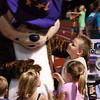 Children meet a mascot on the field.