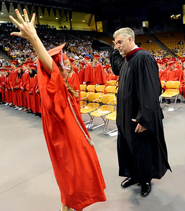 Fairview graduate Anna Burger, left, does the secret student council handshake with principal Don Stensrud after she gets her diploma on Sunday. For more photos and a video, go to www.dailycamera.com. Cliff Grassmick / May 23, 2010