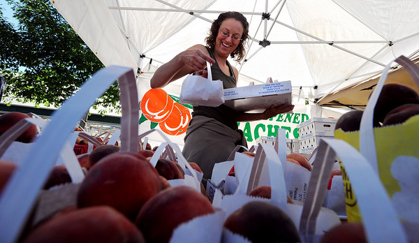 """Darcey Lopez,  of Red Fox Run Ochards, puts out more bags of peaches.<br /> The 2010 Lafayette Peach Festival was held in downtown Lafayette on Saturday.<br /> For more photos and a video of the festival, go to  <a href=""""http://www.dailycamera.com"""">http://www.dailycamera.com</a>.<br /> Cliff Grassmick / August 21, 2010"""