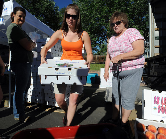 """Sandra Pike of Tate Orchard of Palisade, CO., loads up a box of peaches for Susie Callihan, right, of Broomfield.<br /> The 2010 Lafayette Peach Festival was held in downtown Lafayette on Saturday.<br /> For more photos and a video of the festival, go to  <a href=""""http://www.dailycamera.com"""">http://www.dailycamera.com</a>.<br /> Cliff Grassmick / August 21, 2010"""