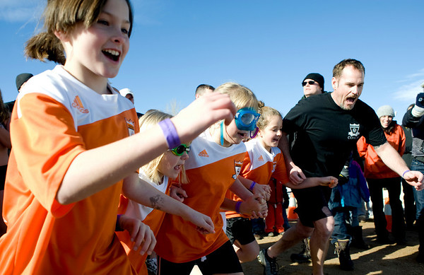 Ryan Abram, 9, runs into the water with the rest of her soccer teammates during the annual Polar Bear Plunge into the Boulder Reservoir New Year's Day, 2010. <br />  <br /> KASIA BROUSSALIAN