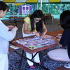Parents helping to sew the S.E.E.D. quilt that the children decorated.