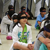 "Children blindfolded waiting for their turn to take the ""trust walk"". I wonder what was in their mind, as they waited in completed darkness."