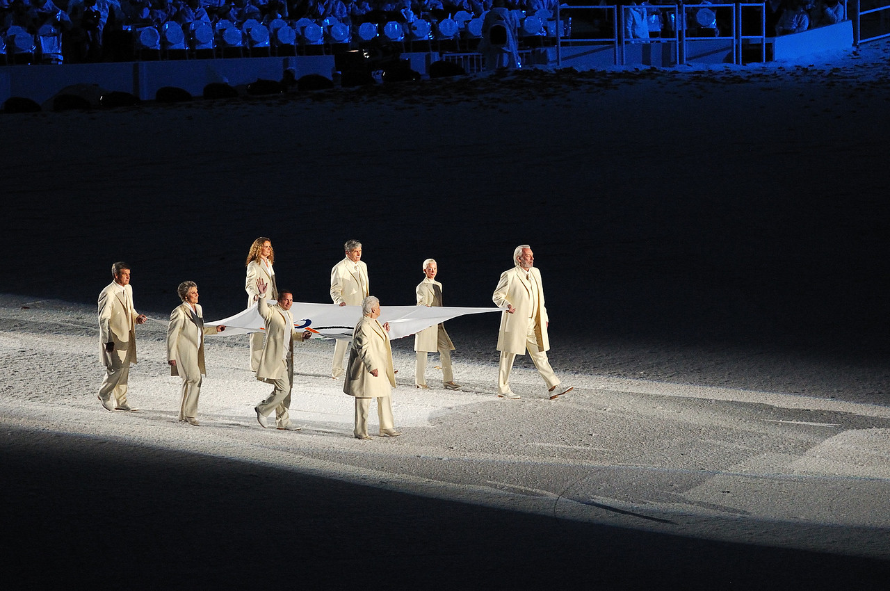 The Olympic flag is carried into the stadium by distinguished Canadians, actor Donald Sutherland, Betty Fox, mother of fundraiser Terry Fox, race car driver Jacques Villeneuve, Olympic figure skater Barbara Ann Scott, singer Anne Murray, former lt.-general Romeo Dallaire, hockey legend Bobby Orr and astronaut Julie Payette.