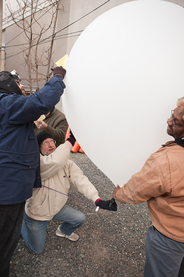 Fearless balloon wranglers write the names of high-dollar pledgers on a balloon.