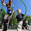 "Susie Ramsey helps her son, Hunter, 2, hula hoop  at the  O Dance  Studio booth.<br /> Pearl Street from 15th to Folsom  was closed to traffic for Boulder Green Streets, a play in the street event on Sunday.<br /> For a video and more photos of the event, go to  <a href=""http://www.dailycamera.com"">http://www.dailycamera.com</a>.<br /> Cliff Grassmick / September 18, 2011"