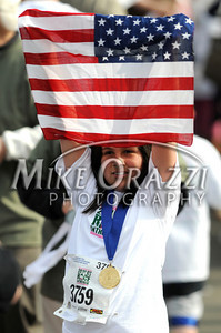 5/7/2011 Mike Orazzi | Staff Tanya Bermejo holds an American flag after finishing the Kids' Challenge 1 Mile Run during the CT Breast Health Initiative Race in the Park at Walnut Hill Park in New Britain on Saturday, May 7, 2011.