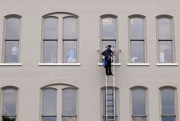 Record-Eagle/Jan-Michael Stump<br /> Moses Ledesma (cq) of Moses Window cleans windows on a Front Street building while workers watch planes fly over West Grand Traverse Bay during Friday's air show practice for the National Cherry Festival, which opens Saturday in Traverse City.