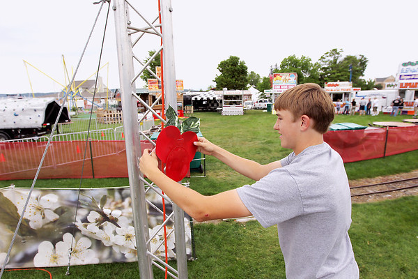 Record-Eagle/Keith King<br /> Austin Olson, 16, of Kingsley, hangs a cherry decoration near Gibbyville Friday, July 1, 2011 in preparation for the National Cherry Festival. Friday's hot, humid weather is not expected to last, said Jeff Halblaub, meteorologist with the National Weather Service in Gaylord. There's a slight chance for wet weather through this afternoon, but once the skies clear, humidity will drop and temperatures will return to normal. Expect highs in the low 80s Sunday and Monday with sunny skies and overnight lows in the upper 50s. For a complete schedule of Saturday's Cherry Festival events, see Page 3A.