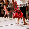 Record-Eagle/Jan-Michael Stump<br /> A model carries a bag from Cherry Hill Boutique during the National Cherry Festival Royale Pageant of Fashion Wednesday at the Park Place Dome.