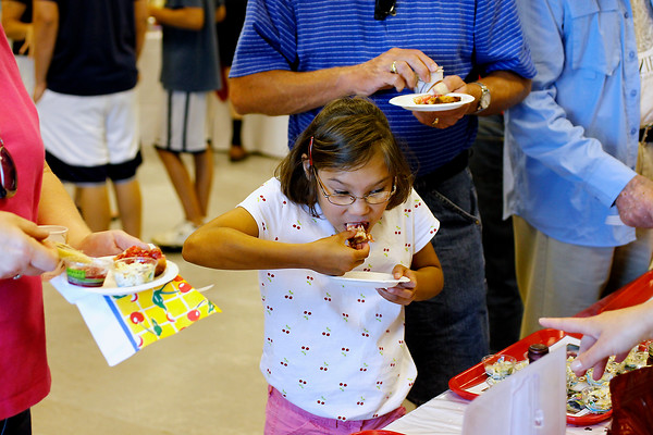 Record-Eagle/Jan-Michael Stump<br /> Elliana Burns (cq), 9, of Reed City samples some of the cherry-themed foods with her mother Polly Burns (cq), left, and father Paul Burns (cq), right, during Friday's Cherry Connection: Bringing Together Festival, Farm and Fruit Friday at the Northwest Michigan Horticultural Research Station operated by Michigan State University.