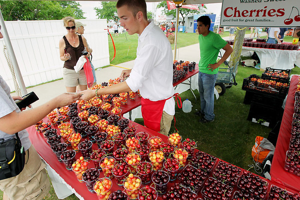 Record-Eagle/Keith King<br /> Kurt Sandmire, an employee with Edmondson Orchards, of Traverse City, sells cherries near the Open Space Saturday, July 2, 2011 during the start of the National Cherry Festival.