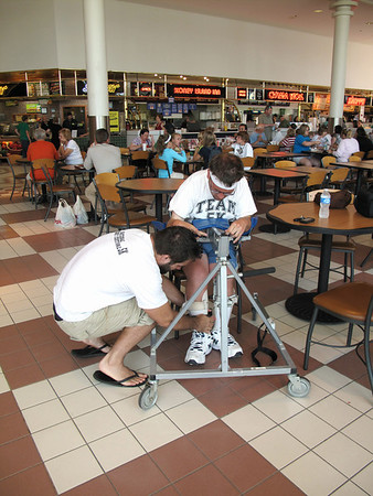 Record-Eagle/Jodee Taylor<br /> Phil Thiel, visiting from Atlanta, helps Grant Forrester, of Traverse City, with his walker at the Grand Traverse Mall. Forrester, a quadriplegic, plans to walk the 5K in Saturday's Festival of Races, part of the National Cherry Festival.