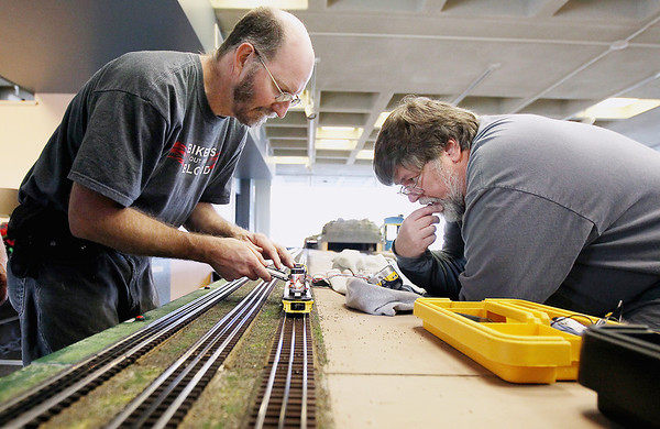 Record-Eagle/Keith King<br /> Jerry Pasman, left, of Interlochen, and John Mallard, of Grawn, make adjustments to the sound system on a model locomotive as preparations are made Saturday, December 10, 2011 by members of the Northern Michigan Railroad Club at the History Center of Traverse City for the Festival of Trains which begins Wednesday, December 14, 2011.