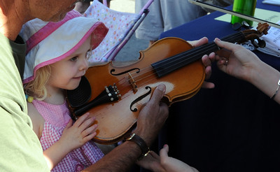 Marlee Foster, 2, tries out a violin at  the 2011 Lafayette Peach Festival on Saturday. For more photos and a  video from the festival, go to www.dailycamera.com Cliff Grassmick / August 20, 2011