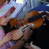 "Marlee Foster, 2, tries out a violin at  the 2011 Lafayette Peach Festival on Saturday.<br /> For more photos and a  video from the festival, go to  <a href=""http://www.dailycamera.com"">http://www.dailycamera.com</a><br /> Cliff Grassmick / August 20, 2011"
