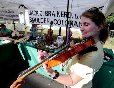 Catherine Millis plays violin at Jack Brainerd's booth at the 2011 Lafayette Peach Festival on Saturday. For more photos and a  video from the festival, go to www.dailycamera.com Cliff Grassmick / August 20, 2011