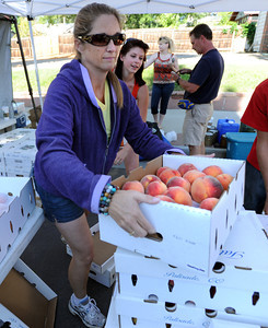 Jody Tate, of Tate Orchards in Palisade, CO, hands out a box of her peaches with the help of her daughter, Sandra, during the 2011 Lafayette Peach Festival on Saturday. For more photos and a  video from the festival, go to www.dailycamera.com Cliff Grassmick / August 20, 2011