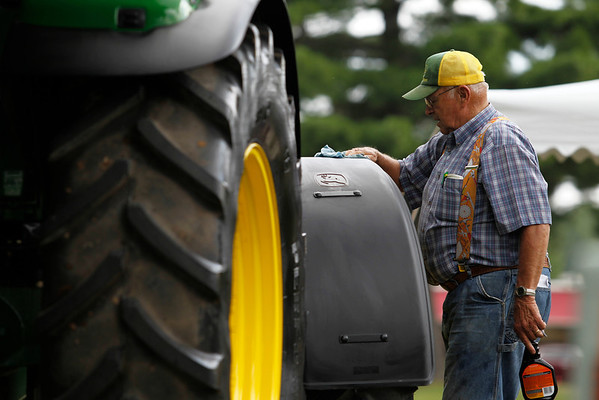 Record-Eagle/Jan-Michael Stump<br /> Martin Woodhams (cq) of Voelker Implement Sales in Lake City cleans a tractor as they set up for the Northwestern Michigan Fair Thursday. Livestock begins arriving on Saturday, and the fair opens with family day on Sunday.