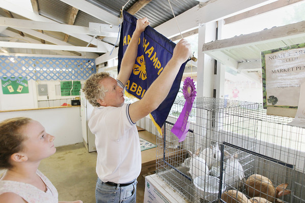 Record-Eagle/Keith King<br /> Kelsey Alpers, 11, of Traverse City, looks on as her father, Randy Alpers, hangs a 4-H 'Grand Champion Rabbit' banner Saturday, August 13, 2011 Kelsey was awarded for her Californian rabbits in the market rabbit division.