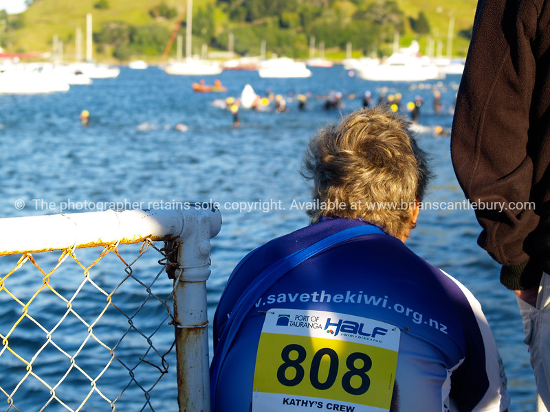 """Port of Tauranga Half Ironman, 2011, contestant 808, member of womens team sits watching swimmers Tauranga is New Zealands 5th largest city and offers a wonderfull variety of scenic and cultural experiences. ALSO SEE; <a href=""""http://www.blurb.com/b/3811392-tauranga"""">http://www.blurb.com/b/3811392-tauranga</a>"""