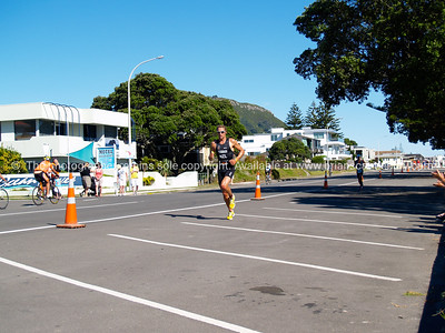 Port of Tauranga Half Ironman, 2011, Shaun Kavanagh rus along Marine Parade. Tauranga is New Zealands 5th largest city and offers a wonderfull variety of scenic and cultural experiences. ALSO SEE; http://www.blurb.com/b/3811392-tauranga