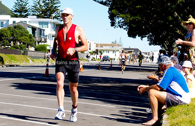Port of Tauranga Half Ironman, 2011, New Zealand. Runner passing spectators on Marine Parade. Tauranga is New Zealands 5th largest city and offers a wonderfull variety of scenic and cultural experiences. ALSO SEE; http://www.blurb.com/b/3811392-tauranga