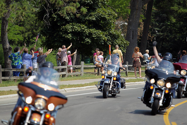 Record-Eagle/Keith King<br /> Spectators wave from Bryant Park in Traverse City as participants in the annual Ride for Father Fred, hosted by the Northern Chapter Harley Owners Group, travel past Sunday, July 17, 2011.
