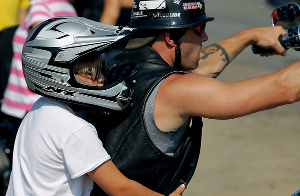 Record-Eagle/Keith King<br /> Andy Vos, of Honor, and his son Aydin Vos, 8, prepare to park their motorcycle Sunday, July 17, 2011 near Classic Motor Sports prior to the start of the annual Ride for Father Fred hosted by the Northern Chapter Harley Owners Group.