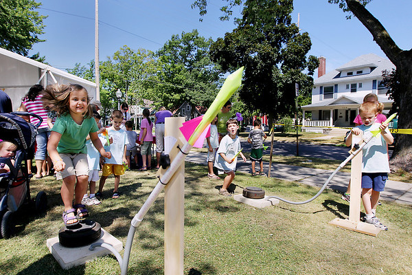 Record-Eagle/Keith King<br /> Lily Gibson, 6, of Traverse City, jumps onto a tire to force air pressure into a rocket he made at the Great Lakes Children's Museum stomp rocket setup Friday, July 29, 2011 during the Traverse City Film Festival Kids Festival at Central Grade School.