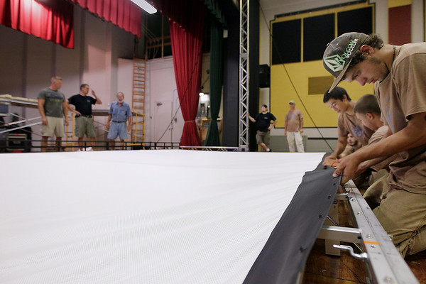Record-Eagle/Keith King<br /> Brandon Kincaid, 18, of Mancelona, and with the SEEDS Youth Conservation Corps, helps snap a projection screen onto its frame prior to being raised in Lars Hockstad Auditorium at Central Grade School Wednesday, July 20, 2011 in preparation for the upcoming annual Traverse City Film Festival.