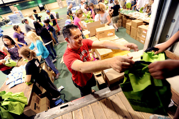 "Volunteer, Bart Taylor, hands up lunches to Peyton Nuechterlein to be put in a truck on Saturday at Balch Fieldhouse.. Over 54,000 lunches were packed for Monday's Bolder Boulder.<br /> For a video and more photos of Bolder Boulder preparations, go to  <a href=""http://www.dailycamera.com"">http://www.dailycamera.com</a>.<br /> Cliff Grassmick / May 26, 2012"