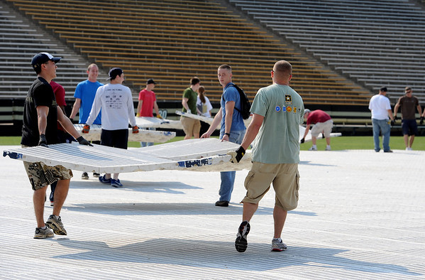 "Dozens of volunteers, some from CU Marine and Navy ROTC, helped put down the tile surface on Folsom Field on Saturday for Monday's Bolder Boulder Race.<br /> For a video and more photos of Bolder Boulder preparations, go to  <a href=""http://www.dailycamera.com"">http://www.dailycamera.com</a>.<br /> Cliff Grassmick / May 26, 2012"