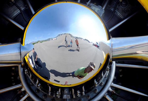 "The reflection of Dave Mulgrew, bottom, can be seen in the 1953 Navy plane at the 7th annual Boulder Airport Day on Saturday.<br /> For more photos and a video of airport day, go to  <a href=""http://www.dailycamera.com"">http://www.dailycamera.com</a>.<br /> Cliff Grassmick / June 16, 2012"