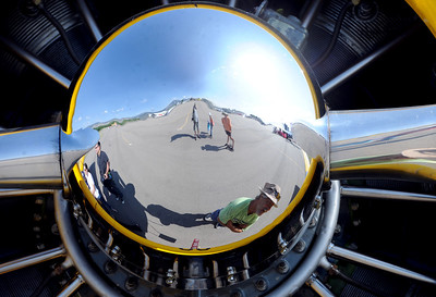 The reflection of Dave Mulgrew, bottom, can be seen in the 1953 Navy plane at the 7th annual Boulder Airport Day on Saturday. For more photos and a video of airport day, go to www.dailycamera.com. Cliff Grassmick / June 16, 2012