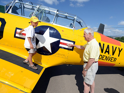 Lawrence Matarrese, 6, gets a close up look at this 1953 Navy plane, owned by Jack Cronin, right, at the 7th annual Boulder Airport Day on Saturday. For more photos and a video of airport day, go to www.dailycamera.com. Cliff Grassmick / June 16, 2012
