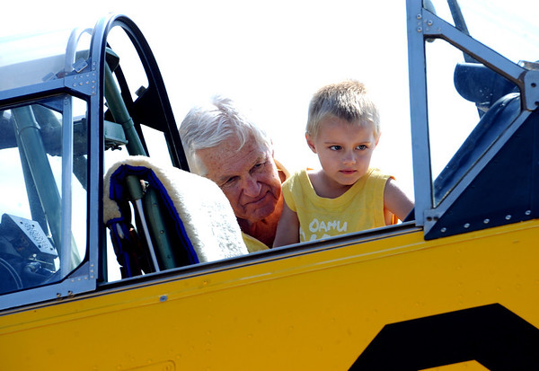 """Pilot and owner, Jack Cronin, holds up Braidon Petersen, 3, to take a closer look at his 1953 Navy plane at the 7th annual Boulder Airport Day on Saturday.<br /> For more photos and a video of airport day, go to  <a href=""""http://www.dailycamera.com"""">http://www.dailycamera.com</a>.<br /> Cliff Grassmick / June 16, 2012"""
